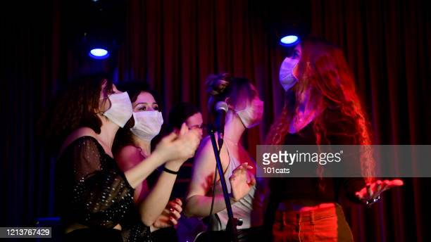 happy young girls singing karaoke together in night club with protective face mask - culture foto e immagini stock