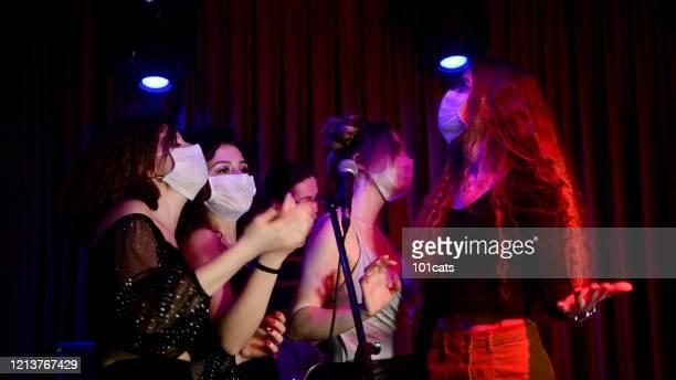 chicas jóvenes felices cantando karaoke juntos en club nocturno con máscara facial protectora - club singer fotografías e imágenes de stock