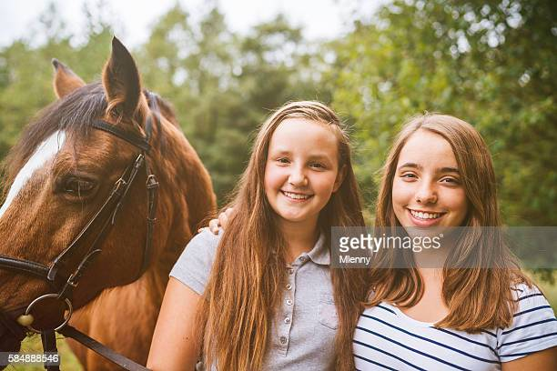 Happy young girls together with their horse