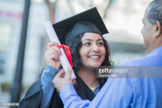 happy young graduate receiving diploma at outdoor ceremony - receiving stock pictures, royalty-free photos & images