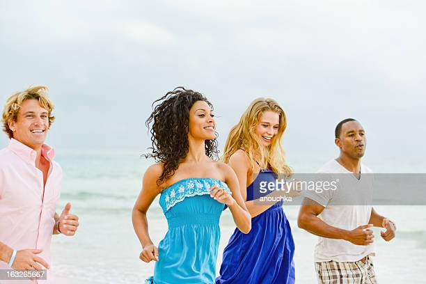 Happy Young Group of Friends Running on the Beach