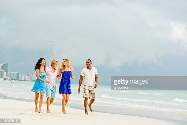 Happy Young Group of Friends Walking on the Beach