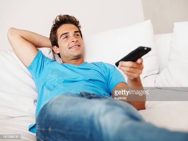 Happy young guy relaxing with remote control in hand