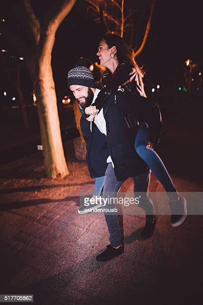 Happy young hipster couple having nighttime fun in the city