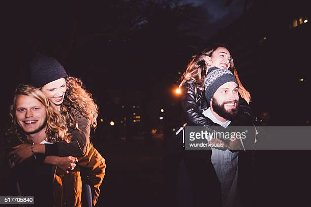 Happy young hipster couples having piggyback rides at night