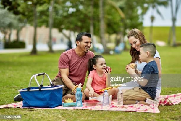 公園で一緒に時間を過ごす幸せな若いヒスパニック家族 - ピクニック ストックフォトと画像