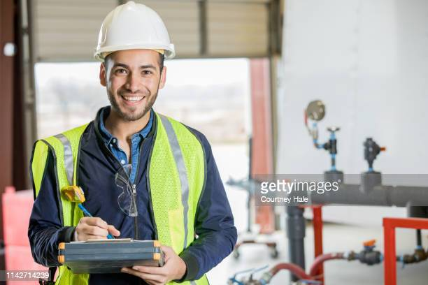 happy young hispanic man working as engineer in oil and gas industry smiles at camera - inspector stock pictures, royalty-free photos & images