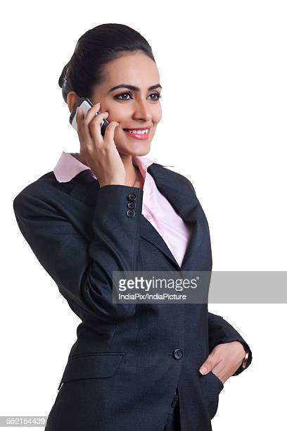 Happy young Indian businesswoman using cell phone over white background