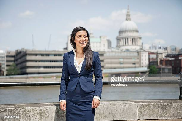 Happy young Indian businesswoman with St. Paul's Cathedral in background