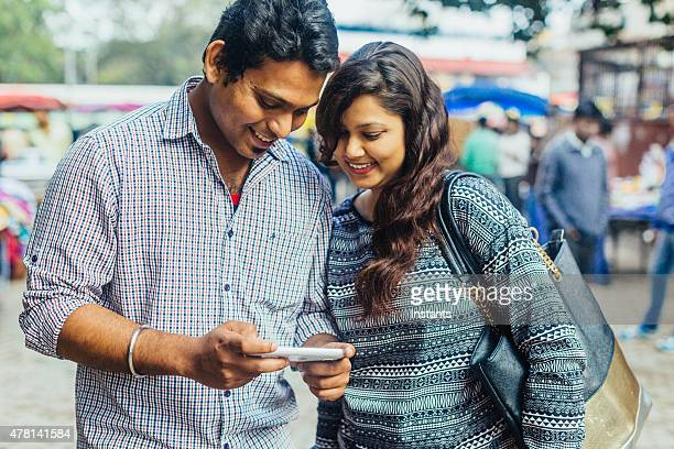 Happy young Indian Couple looking at Mobile