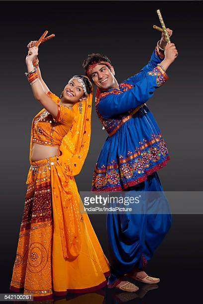 Happy young Indian couple performing Dandiya Raas over black background