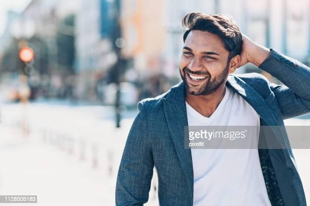 feliz etnia indiana jovem homem na rua - mão no cabelo - fotografias e filmes do acervo