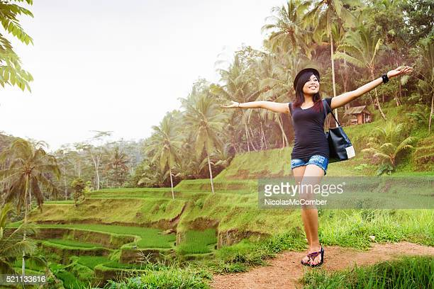 Happy young Indonesian woman proudly shows off Bali landscape