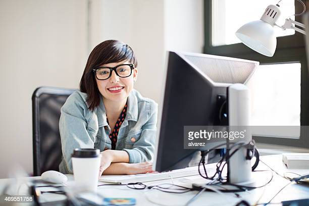 Happy young IT professional at her desk