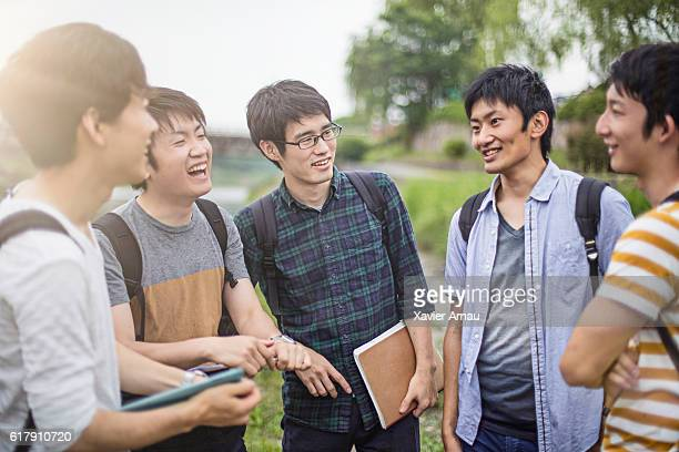 Happy young japanese students talking outdoors