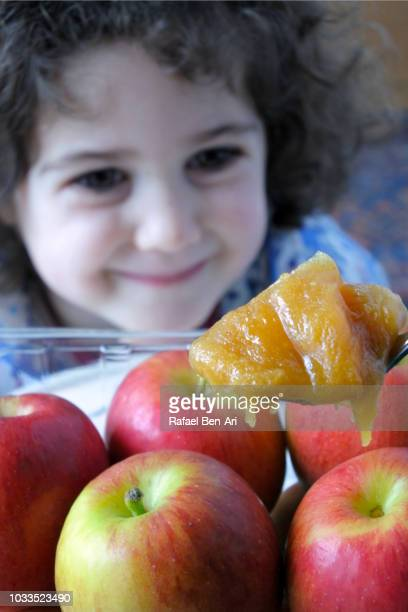 happy young jewish girl  looking at large honey scoop with apples - rafael ben ari - fotografias e filmes do acervo