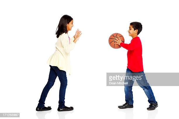 Happy young kids playing basketball