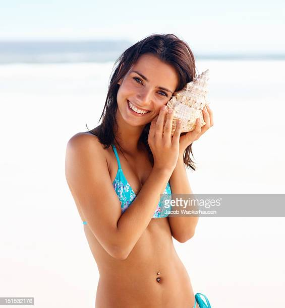 happy young lady holding a shell - conch shell stock pictures, royalty-free photos & images