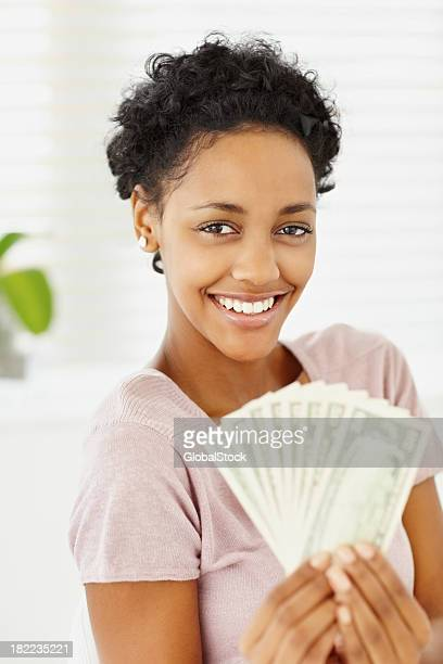 Happy young lady holding currency notes