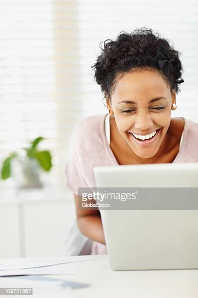 Happy young lady using a laptop