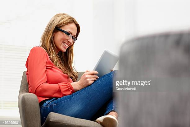 Happy young lady wearing smart glasses using tablet
