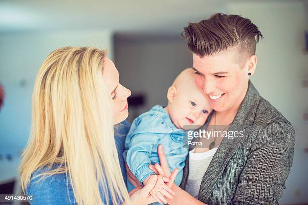 Happy young lesbian couple with baby at home