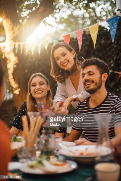 happy young male and female friends at table during dinner party in backyard - invité photos et images de collection