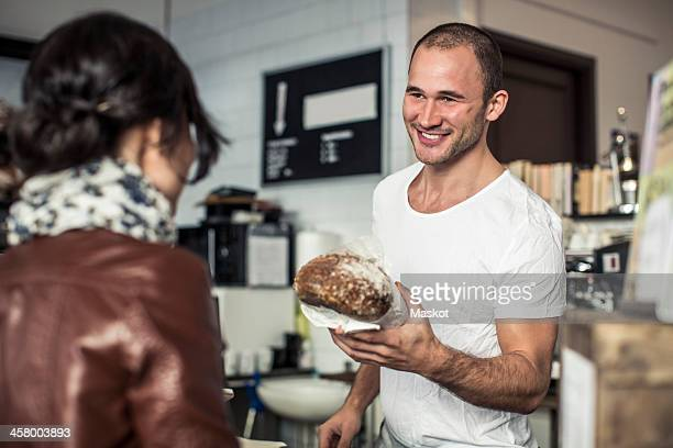 Happy young male owner giving bread loaf to customer in bakery