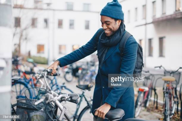 Happy young male university student standing by bicycle in city