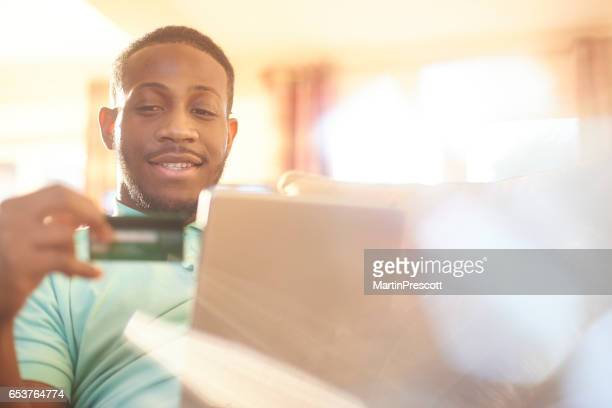 Happy young male using credit card to do online shopping