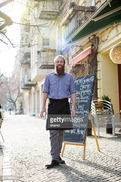 Happy young male waiter standing outside cafe