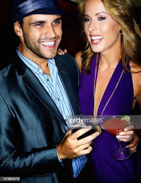 Happy young man and woman having drinks together against black