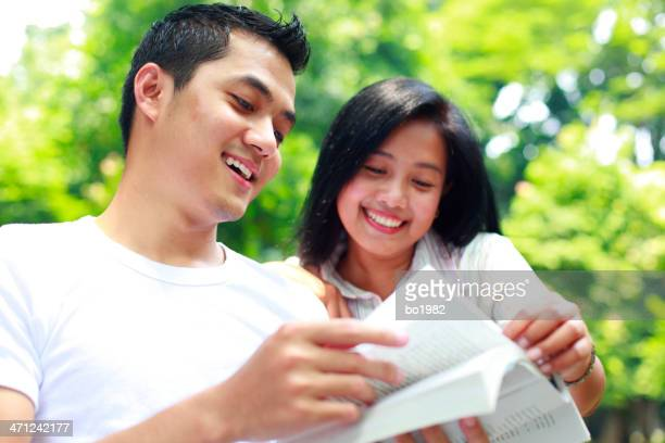 happy young man and woman reading book