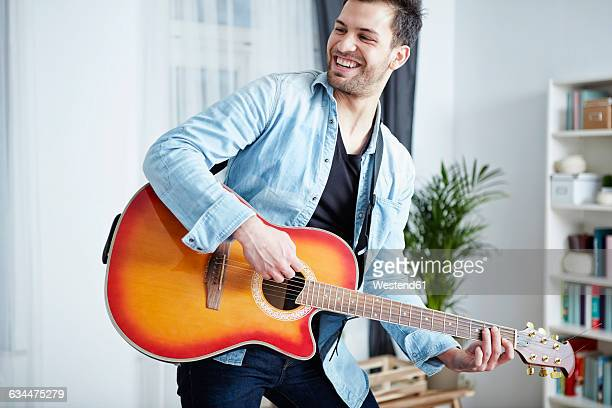 Happy young man at home playing guitar