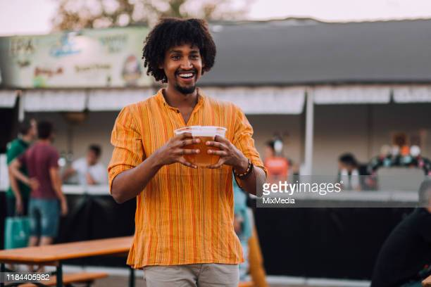 happy young man bought beer for his festival friends - carrying stock pictures, royalty-free photos & images