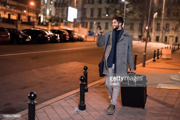 happy young man calling taxi on city street. - sharing economy stock pictures, royalty-free photos & images