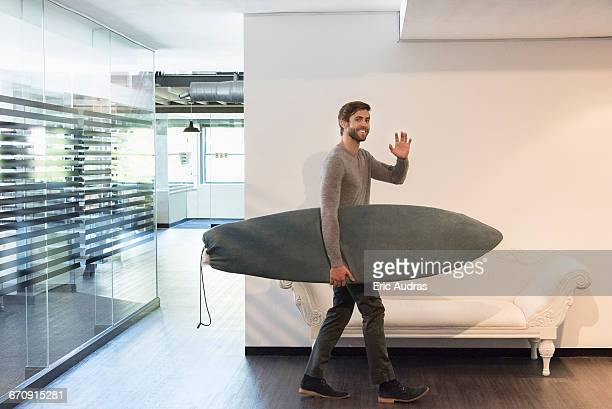 happy young man carrying a surfboard at home - winken stock-fotos und bilder