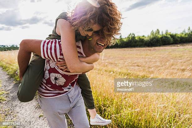 Happy young man carrying girlfriend piggyback on field path