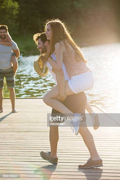 Happy young man carrying girlfriend piggyback on jetty at a lake
