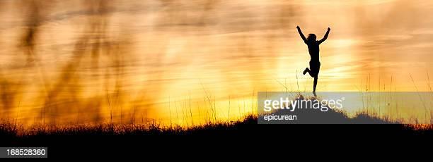 幸せな若い男性のお祝いの丘の上に沈む夕日