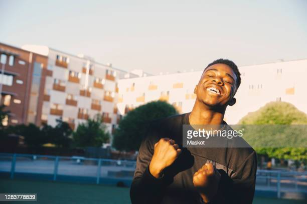 happy young man cheering with eyes closed in sports field - adolescence stock pictures, royalty-free photos & images