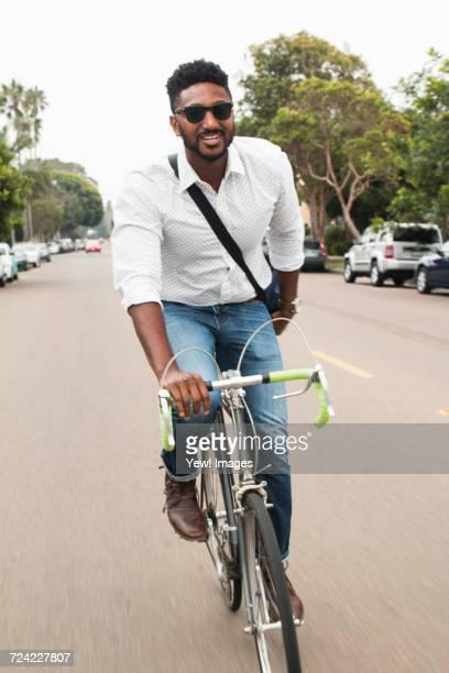Happy young man cycling along road
