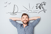 Happy young man dreaming about vacation. Drawn picture of seaside overhead