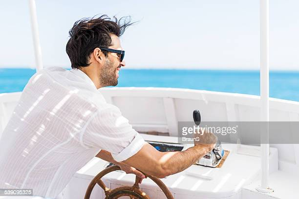 Happy young man driving a boat.