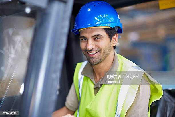Happy young man driving a forklift truck