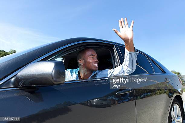 A happy young man driving and waving