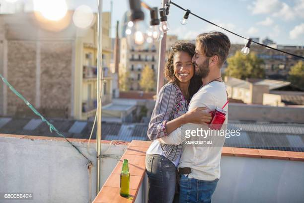 Happy young man embracing woman on terrace