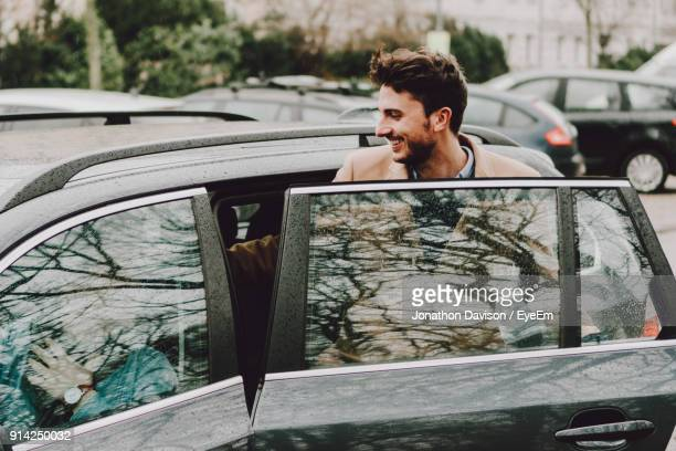 happy young man entering wet car in city during rainy season - entrata foto e immagini stock