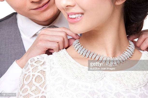 Happy young man fastening young woman's diamond necklace