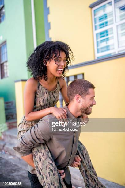 Happy young man giving girlfriend a piggyback ride